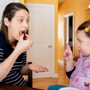 Mom eating frozen cherry while toddler daugther tries to scold her