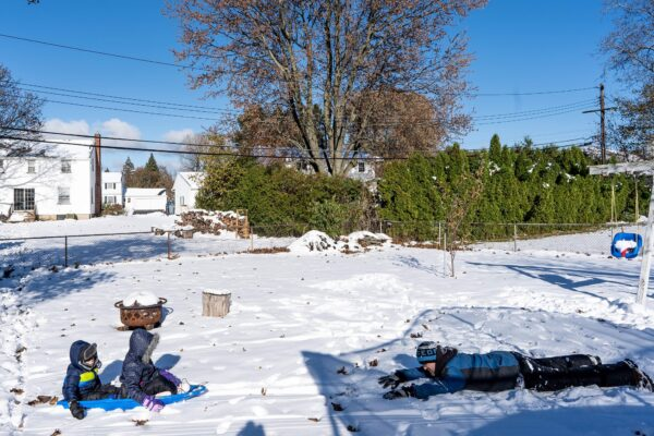 Children playing on sled with Dad after snow storm by Rochester NY Documentary Family Photographer Gabriella Hunt